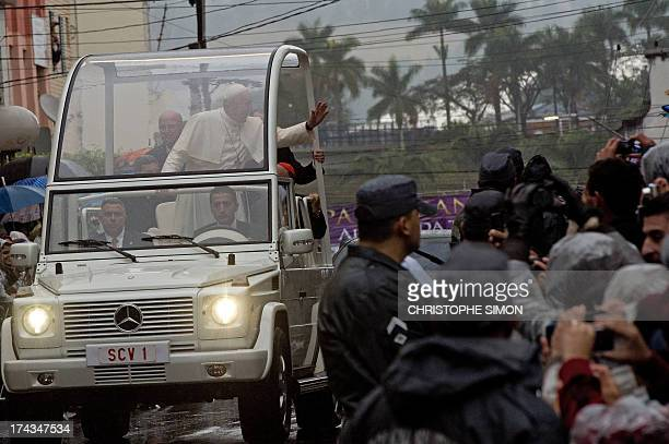 Pope Francis waves at faithfuls from the popemobile under heavy rain after giving a mass at the Basilica of Our Lady of Aparecida Brazil's most...