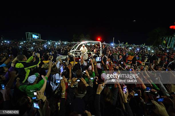 Pope Francis waves at faithfuls standing along the beachfront in Rio de Janeiro on his way for a prayer vigil with hundreds of thousands of young...