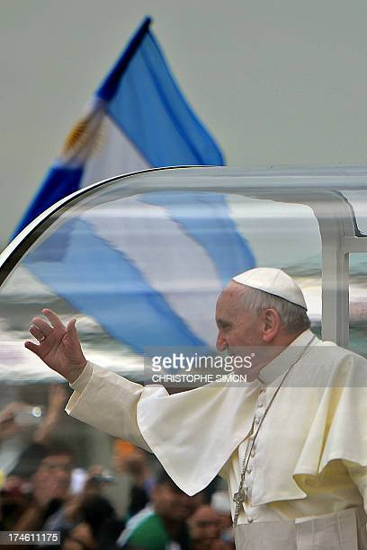 Pope Francis waves at faithfuls standing along the beachfront in Rio de Janeiro as hundreds of thousands of Catholic pilgrims attending World Youth...