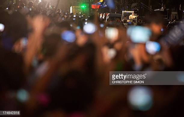 Pope Francis waves at faithfuls standing on the beachfront as he arrives on the popemobile at Copacabana beach to participate in a reenactment of the...