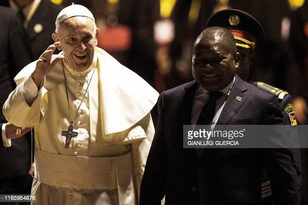 Pope Francis waves at the crowd next to Mozambican President Felipe Nyusi upon his arrival at the Maputo International Airport on September 4, 2019...