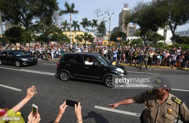 Pope Francis waves at the people standing on the sides of the street as he heads to the Las Palmas air base in Lima where he will celebrate mass on...
