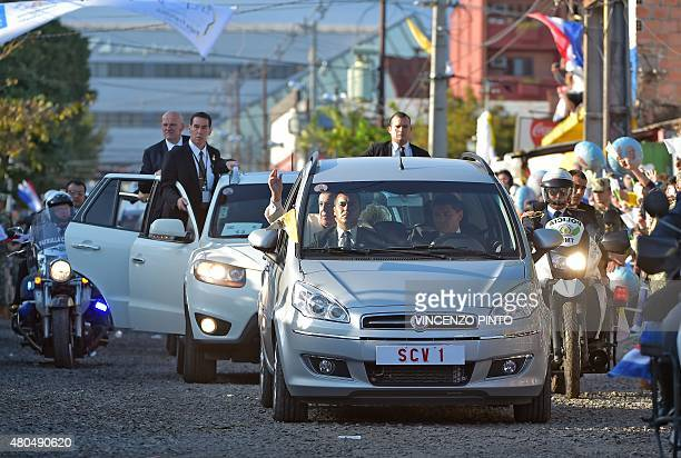 Pope Francis waves from a car as he arrives for a visit to the people of Banado Norte at the Chapel of Juan Bautista in Asuncion on July 12, 2015....