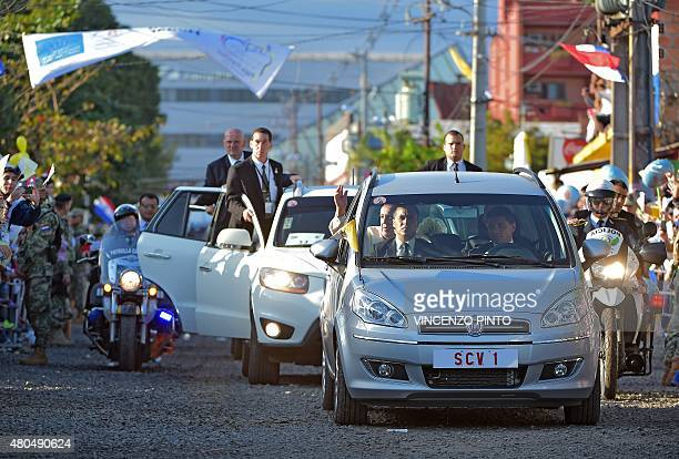 Pope Francis waves from a car as he arrives for a visit to the people of Banado Norte at the Chapel of Juan Bautista in Asuncion on July 12 2015 Pope...