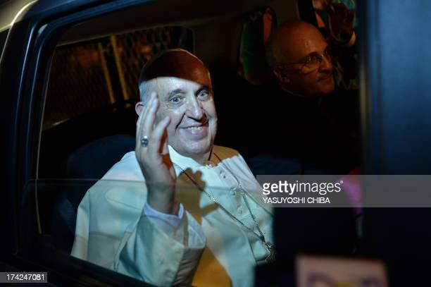 Pope Francis waves from the car as he leaves the Guanabara Palace seat of the city's government in Rio de Janeiro after the welcoming ceremony...