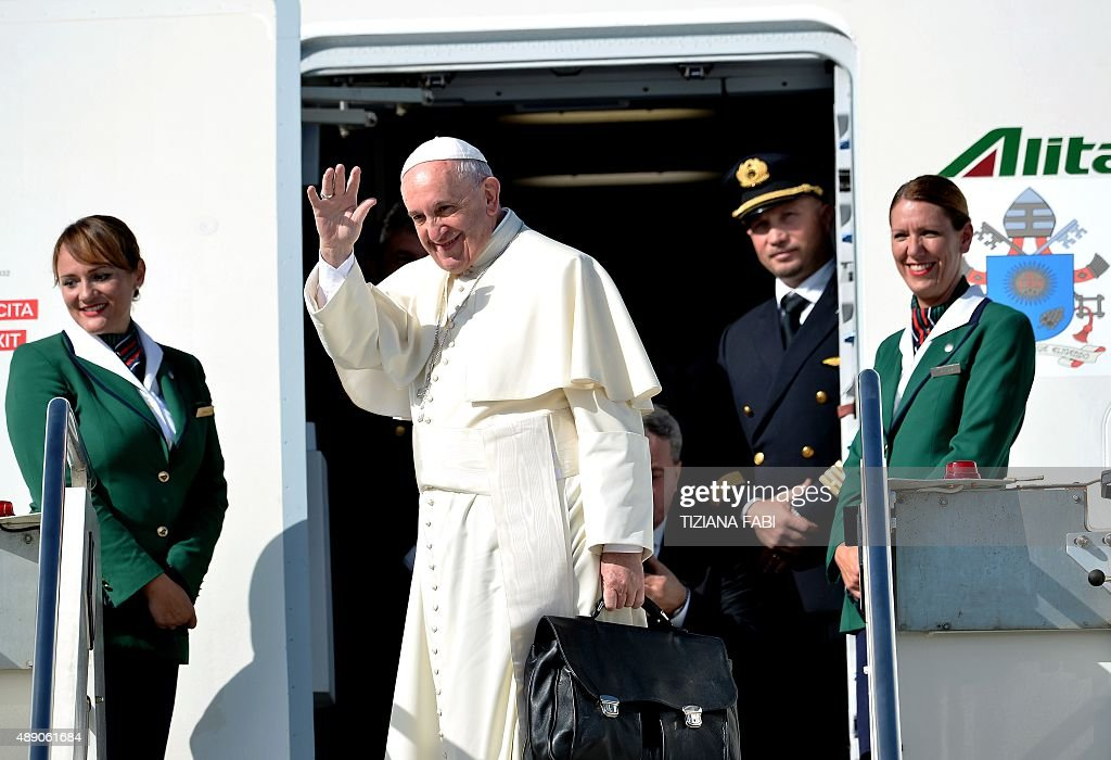 Pope Francis waves from the plane's steps upon his arrival at the Rome's Fiumicino airport on September 19, 2015. The pontiff heads for Cuba on September 19 on the first-leg of a trip that will also take him to the United States for his most high-profile overseas visit to date.