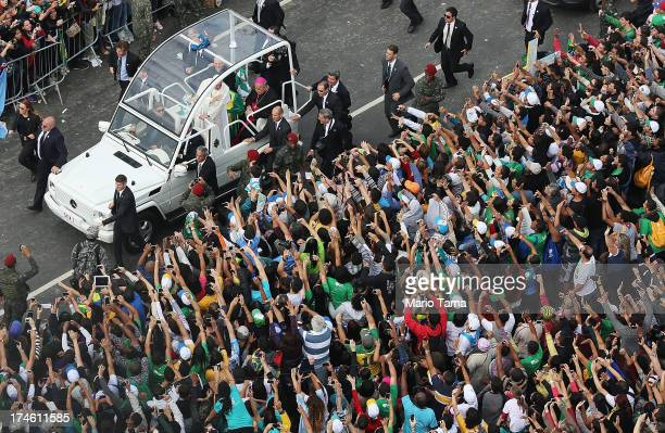 Pope Francis waves from the Popemobile as he arrives to celebrate Mass on Copacabana Beach during World Youth Day celebrations on July 28, 2013 in...