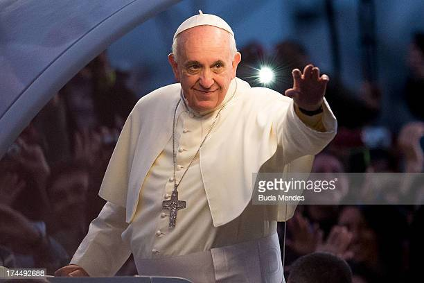 Pope Francis waves from the Popemobile on his way to attend the Via Crucis on Copacabana Beach during World Youth Day celebrations on July 26, 2013...
