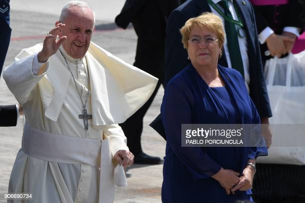 Pope Francis waves next to Chilean President Michelle Bachelet as he gets ready to board the plane to leave the northern Chilean city of Iquique...