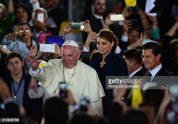Pope Francis waves next to Mexican President Enrique Pena Nieto and First Lady Angelica Rivera as he arrives at the airport in Ciudad Juarez...