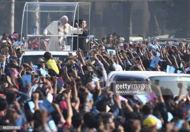 Pope Francis waves to Bangladeshi Christians as he arrives to lead mass in Dhaka on December 1 2017 Pope Francis arrived in Bangladesh from Myanmar...