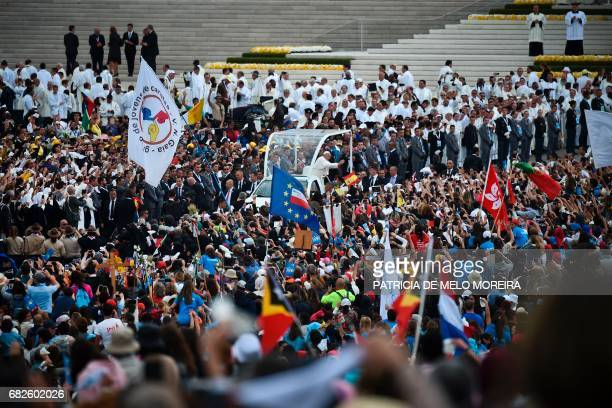Pope Francis waves to faithful from the popemobile as he bids farewell during his visit to Fatima shrine, in Fatima, on May 13, 2017. The two young...