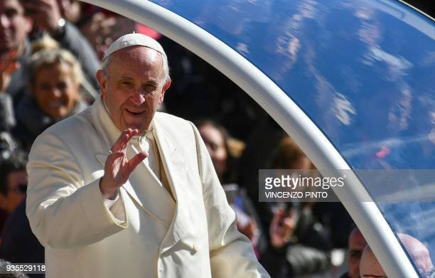 Pope Francis waves to faithful upon his arrival in St Peter's square in Vatican for his weekly general audience on March 21 2018 / AFP PHOTO /...