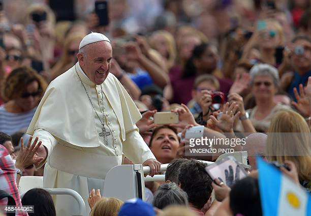 Pope Francis waves to faithful upon his arrival on St Peter's square at the Vatican to lead his weekly general audience on September 16 2015 AFP...