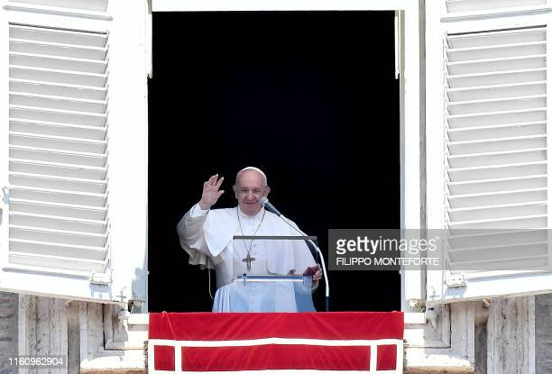 Pope Francis waves to pilgrims from his studio window overlooking St Peter's Square at the Vatican during the Sunday Angelus prayer on August 11 2019