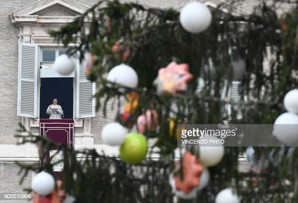 Pope Francis waves to pilgrims gathered in Saint Peter's square during his Angelus Sunday prayer at the Vatican on December 31 2017 / AFP PHOTO /...