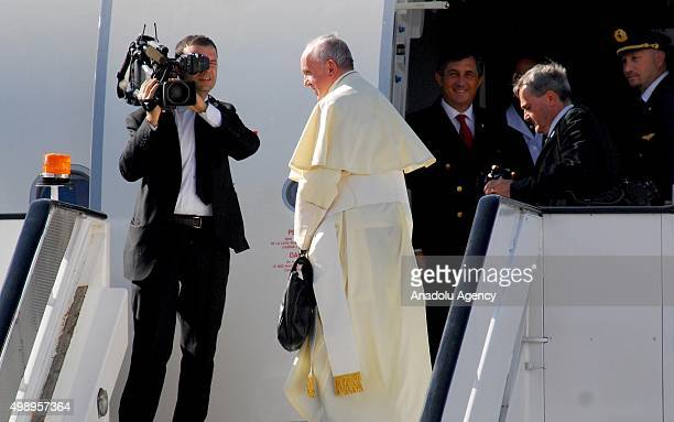 Pope Francis waves to the Catholic faithful as he boards his plane at Jomo Kenyatta International Airport on November 27 2015 in Nairobi on his way...