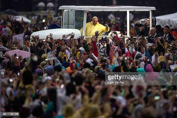 Pope Francis waves to the crowd after conducting mass at the Rizal Park on January 18 2015 in Manila Philippines Pope Francis will visit venues...