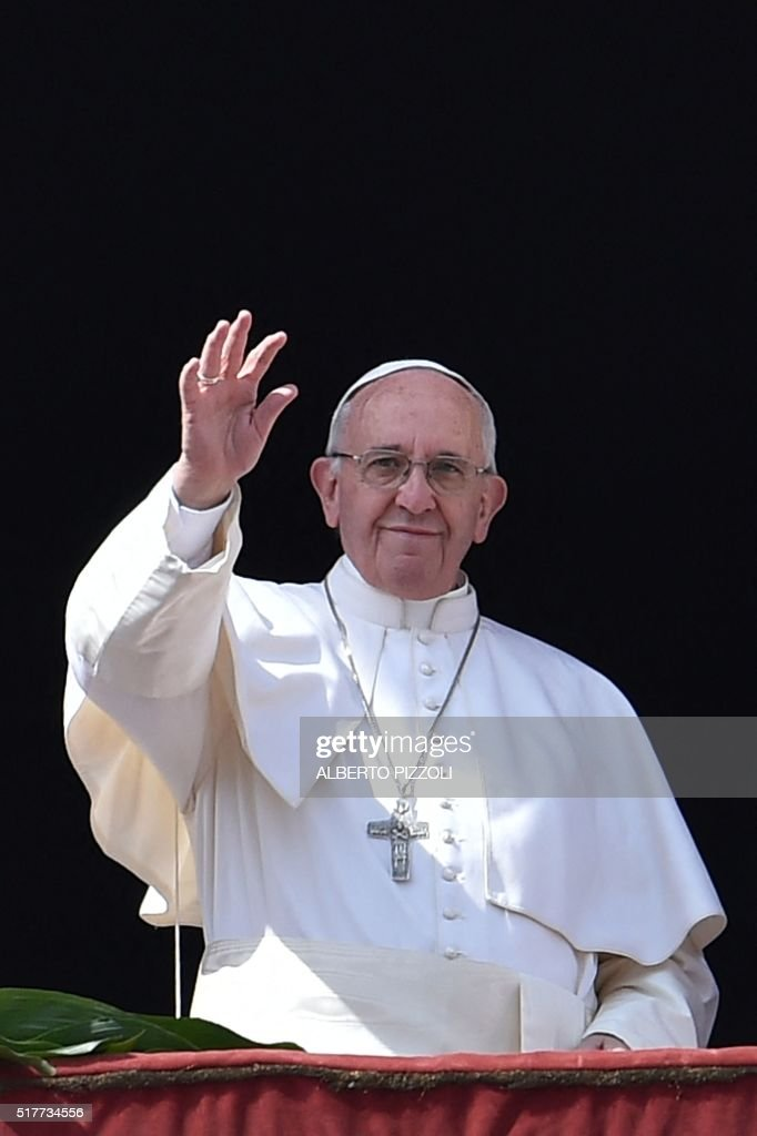 Pope Francis waves to the crowd after the 'Urbi et Orbi' blessing for Rome and the world from the central loggia of St Peters' basilica following the Easter Sunday mass on March 27, 2016 at St Peter's square in Vatican. Christians around the world are marking the Holy Week, commemorating the crucifixion of Jesus Christ, leading up to his resurrection on Easter.