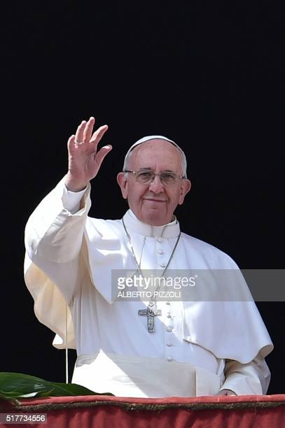 Pope Francis waves to the crowd after the Urbi et Orbi blessing for Rome and the world from the central loggia of St Peters' basilica following the...