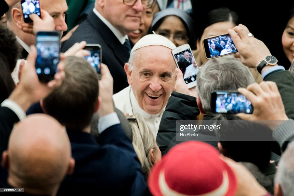 Pope Francis waves to the crowd as he arrives for his weekly general audience in the Paul VI Hall at the Vatican, Wednesday, Dec. 6, 2017.