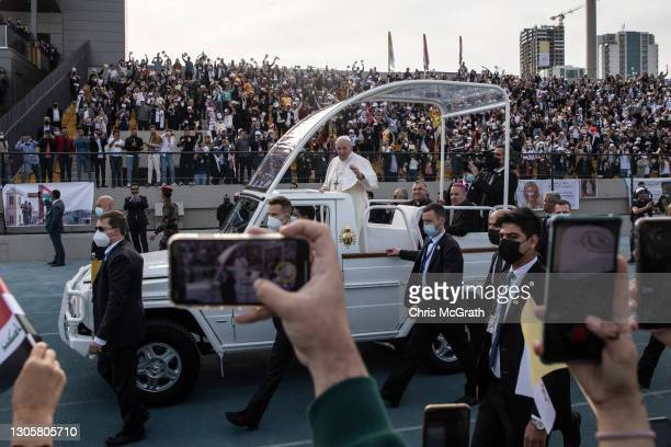 Pope Francis waves to the crowd as he arrives to conduct mass at the Franso Hariri Stadium on March 07, 2021 in Erbil, Iraq. Pope Francis arrived in...