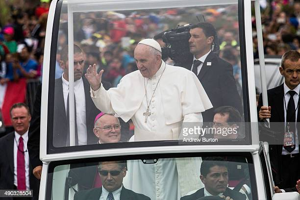 Pope Francis waves to the crowd from his popemobile while on his way to lead Mass at Benjamin Franklin Parkway on September 27 2015 in Philadelphia...