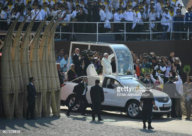 Pope Francis waves to the crowd from the popemobile as he arrives to officiate an open-air mass at the beach resort town of Huanchaco - northwest of...