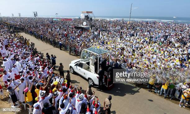 Pope Francis waves to the crowd from the popemobile as he arrives to officiate an openair mass at the beach resort town of Huanchaco northwest of the...