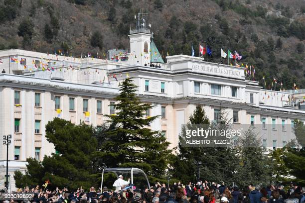 Pope Francis waves to the crowd from the popemobile near the Casa sollievo della Sofferenza' hospital in San Giovanni Rotondo on March 17 2018 during...