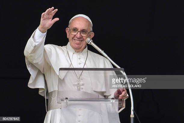 Pope Francis waves to the crowd from the window of the Apostolic palace overlooking StPeter's square during his Sunday Angelus prayer on January 10...