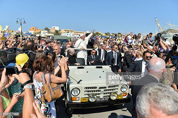 Pope Francis waves to the faithful as he arrives in the island on July 8, 2013 in Lampedusa, Italy. On his first official trip outside Rome, Pope...