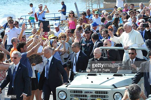 Pope Francis waves to the faithful as he arrives in the island on July 8 2013 in Lampedusa Italy On his first official trip outside Rome Pope Francis...