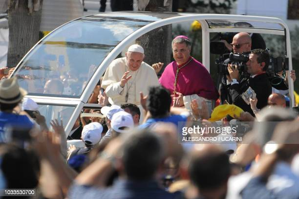 Pope Francis waves to the faithful as he arrives in the popemobile along with Archbishop of Palermo Corrado Lorefice at the Foro Italico seafront...