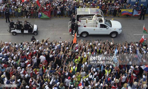 Pope Francis waves to the faithful as he arrives in the popemobile for his welcome ceremony at Campo Santa Maria La Antigua in Panama City during...