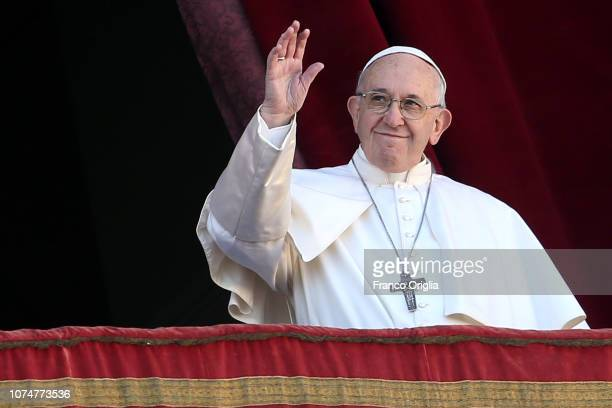 Pope Francis waves to the faithful as he delivers his Christmas 'Urbi et Orbi' blessing message from the central balcony of St Peter's Basilica on...