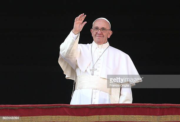 Pope Francis waves to the faithful as he delivers his 'Urbi et Orbi' blessing message from the central balcony of St Peter's Basilica on December 25...