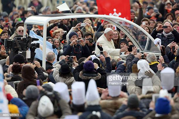 Pope Francis waves to the faithful as he holds his weekly audience in St Peter's Square on January 29 2014 in Vatican City Vatican After his...