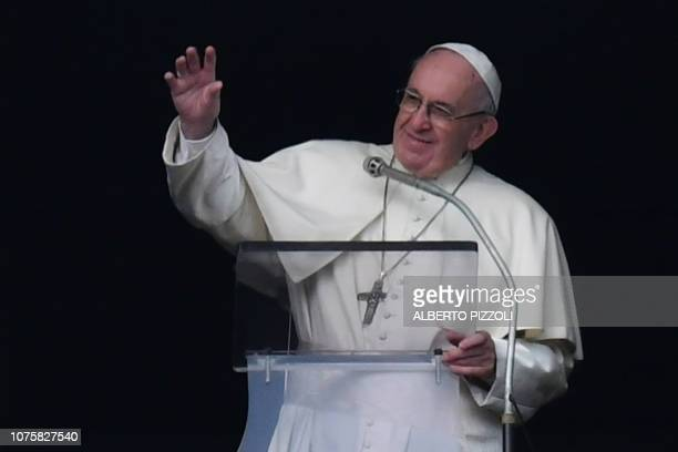 Pope Francis waves to the faithful from the window of the Apostolic Palace overlooking St Peter's square during the weekly Angelus prayer on December...