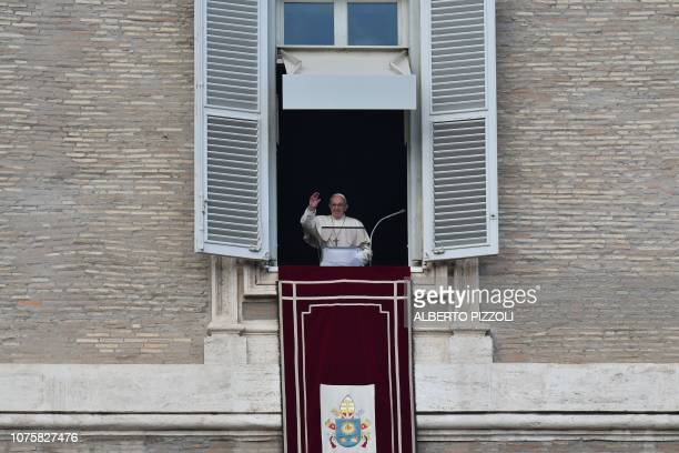 Pope Francis waves to the faithful upon his arrival at the window of the Apostolic Palace overlooking St Peter's square for the weekly Angelus prayer...