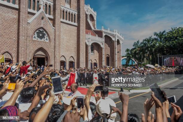 Pope Francis waves to wellwishers as he exits St Mary's Cathedral after a mass in Yangon on the last day of a fourday visit on November 30 2017 Pope...