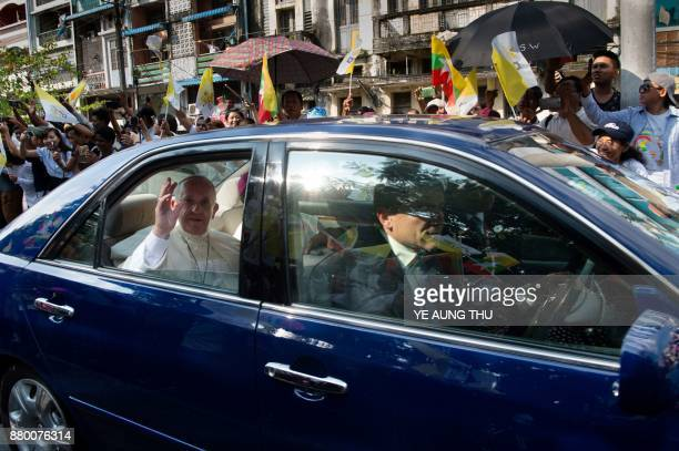 Pope Francis waves to wellwishers as he is driven through the streets of downtown Yangon on November 27 2017 Pope Francis arrived in mainly Buddhist...