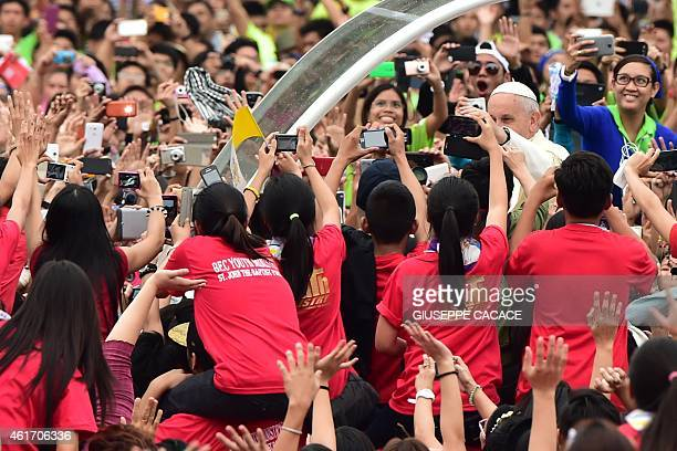 Pope Francis waves to worshippers holding cameras as he arrives at the University of Santo Tomas during his visit to Manila on January 18 2015 Pope...