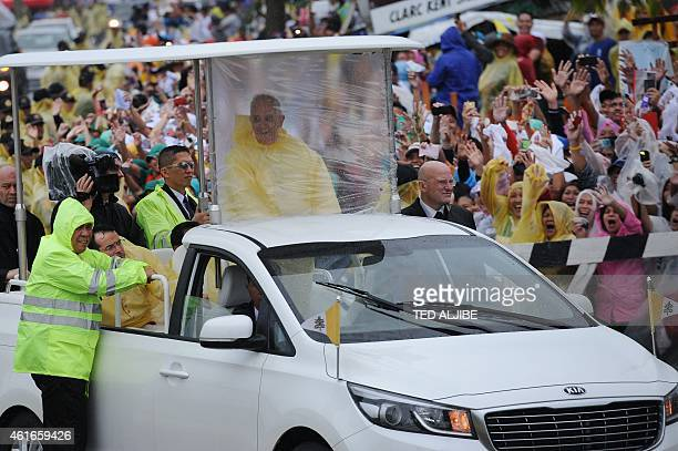 Pope Francis , wearing a yellow raincoat, smiles at the crowd as he travels from Tacloban airport to the town of Palo after celebrating mass on...