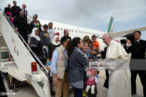 Pope Francis welcomes a group of Syrian refugees after landing at Ciampino airport in Rome following a visit at the Moria refugee camp on April 16...