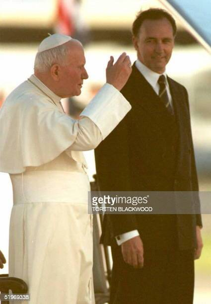 Pope John Paul II blesses the faithful upon his arrival in Sydney 18 January as Australian Prime Minister Paul Keating looks on The Pope was greeted...