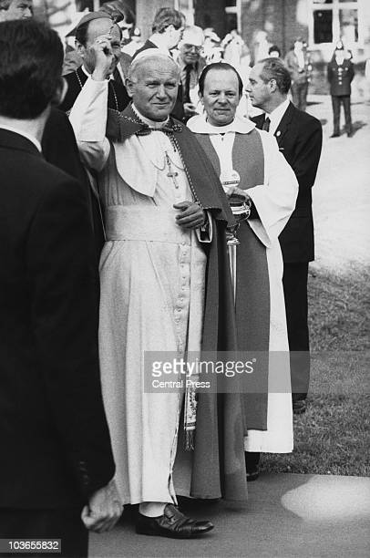 Pope John Paul II conducts a blessing with holy water during a visit to Digby Stuart Catholic College, Roehampton, London, 29th May 1982.