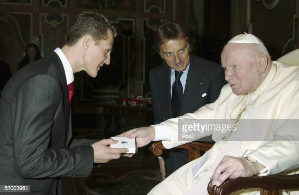 Pope John Paul II gives a gift to the Formula One world champion Michael Schumacher of Germany as Ferrari President Luca Cordero di Montezemolo looks...