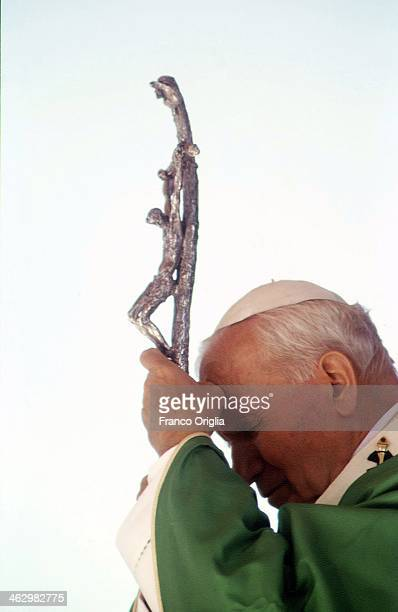 Pope John Paul II holds his crucifix during his official visit to the Italian region of Aosta Valley where he is spending his holiday on August 21...