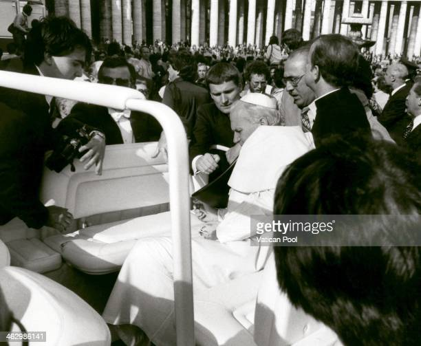 Pope John Paul II is helped by his bodyguards and by senior officer of the Swiss Guard Alois Estermann after being shot by Mehmet Ali Agca at St...